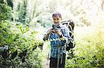 Hiker taking photo with camera phone in forest