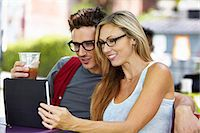 Couple using digital tablet at cafe Stock Photo - Premium Royalty-Freenull, Code: 614-07806298