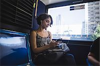 Young woman commuting on bus listening to music on smartphone, New York, US Stock Photo - Premium Royalty-Freenull, Code: 614-07806450