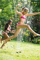 Girls in swimming costume jumping over garden sprinkler Stock Photo - Premium Royalty-Freenull, Code: 614-07806471