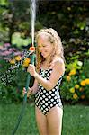 Girl in swimming costume playing with garden hose