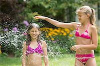 Girls in swimming costume playing with garden sprinkler Stock Photo - Premium Royalty-Free