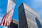 Low angled view of skyscrapers and American flag in financial district, Manhattan, New York, USA