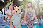 Family with two children walking by swimming pool
