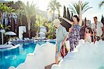 Happy family with two children walking by resort swimming pool