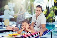 Portrait of smiling father and daughter relaxing by swimming pool, mother and daughter in background Stock Photo - Premium Royalty-Freenull, Code: 6113-07808130