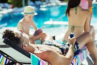 Family with two children sunbathing by resort swimming pool Stock Photo - Premium Royalty-Freenull, Code: 6113-07808140
