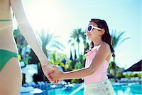 Mother and daughter holding hands by swimming pool Stock Photo - Premium Royalty-Freenull, Code: 6113-07808141