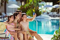 Family with two children taking selfie by swimming pool Stock Photo - Premium Royalty-Freenull, Code: 6113-07808149