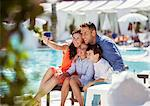 Family with two children taking selfie by resort swimming pool
