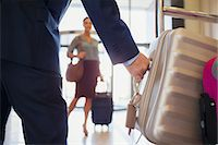 Close up of man wearing suit grabbing silver suitcase, woman in background Stock Photo - Premium Royalty-Freenull, Code: 6113-07808532