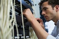 Computer technician performing maintenance on computer networking equipment Stock Photo - Premium Royalty-Freenull, Code: 632-07809331