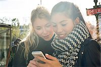 Young women outdoors looking at cell phone together Stock Photo - Premium Royalty-Freenull, Code: 632-07809378