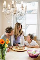 family table eating together - Family eating pizza and salad at home Stock Photo - Premium Royalty-Freenull, Code: 6121-07809847