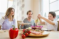 family table eating together - Family eating pizza and salad at home Stock Photo - Premium Royalty-Freenull, Code: 6121-07809848