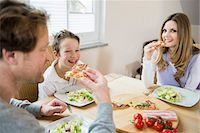 family table eating together - Family eating pizza and salad at home Stock Photo - Premium Royalty-Freenull, Code: 6121-07809851