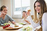 family table eating together - Family eating pizza and salad at home Stock Photo - Premium Royalty-Freenull, Code: 6121-07809852