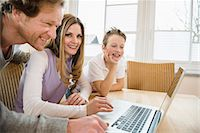 Family using laptop at home Stock Photo - Premium Royalty-Freenull, Code: 6121-07809867