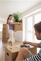 Woman carrying heavy box man eating lazy Stock Photo - Premium Royalty-Freenull, Code: 6121-07809977