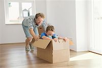 pushing - Father son new apartment playing cardboard box Stock Photo - Premium Royalty-Freenull, Code: 6121-07809995
