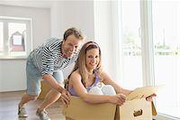 pushing - Man pushing woman inside box new home Stock Photo - Premium Royalty-Freenull, Code: 6121-07810001
