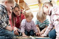 Female educator and four kids looking at picture book Stock Photo - Premium Royalty-Freenull, Code: 6121-07810105