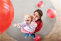 Female educator and little girl playing with red balloons in kindergarten Stock Photo - Premium Royalty-Freenull, Code: 6121-07810111