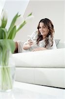 Portrait of smiling young woman with smartphone lying on couch at home Stock Photo - Premium Royalty-Freenull, Code: 6121-07810164