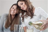 Young woman pouring champage into glasses while her female friend watching Stock Photo - Premium Royalty-Freenull, Code: 6121-07810182