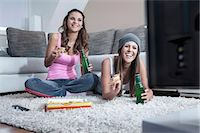 Two female friends side by side on carpet at home watching television Stock Photo - Premium Royalty-Freenull, Code: 6121-07810202