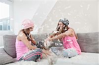 funny looking people - Two female friends sitting on couch at home having pillow fight Stock Photo - Premium Royalty-Freenull, Code: 6121-07810206