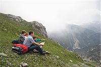 Father and kids looking at hiking map mountains Stock Photo - Premium Royalty-Freenull, Code: 6121-07810266
