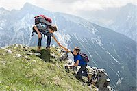 Teenage boys helping friend climbing in mountains Stock Photo - Premium Royalty-Freenull, Code: 6121-07810268