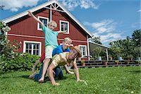 Father and sons playing in garden house Stock Photo - Premium Royalty-Freenull, Code: 6121-07810395