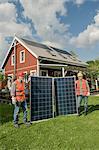 Two workmen holding solar panel garden