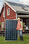 Timber house workman solar panel portrait