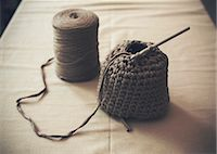 Half-finished woolen purse with spool on table Stock Photo - Premium Royalty-Freenull, Code: 698-07812929