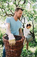 Man carrying wicker basket with woman gardening in background at yard Stock Photo - Premium Royalty-Freenull, Code: 698-07812946