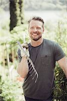 Happy man looking away while carrying gardening fork on shoulder at yard Stock Photo - Premium Royalty-Freenull, Code: 698-07812957