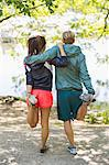 Full length rear view of couple doing stretching exercises together at lakeshore