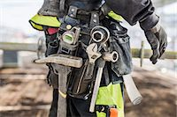Midsection of construction worker wearing tool belt at site Stock Photo - Premium Royalty-Freenull, Code: 698-07813100
