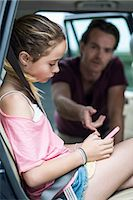 prevention - Daughter ignoring father while using mobile phone in car Stock Photo - Premium Royalty-Freenull, Code: 698-07813173