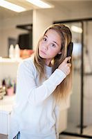 Girl combing hair at home Stock Photo - Premium Royalty-Freenull, Code: 698-07813178