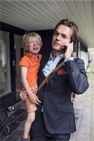 Businessman using mobile phone while carrying crying son outside house Stock Photo - Premium Royalty-Freenull, Code: 698-07813186