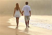 Back view of a couple walking and holding hands on the sand of a beach at sunset Stock Photo - Royalty-Freenull, Code: 400-07825928