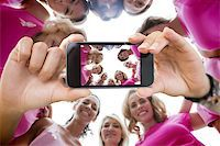 Composite image of hand holding smartphone showing photograph of breast cancer activists Stock Photo - Royalty-Freenull, Code: 400-07834656