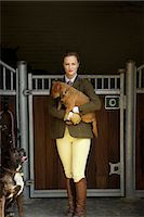 equestrian - Woman in Riding Outfit Standing in front of Stable Carrying Dog in her Arms Stock Photo - Premium Rights-Managednull, Code: 822-07840870