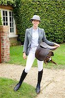 Woman in Riding Outfit Holding Saddle Stock Photo - Premium Rights-Managednull, Code: 822-07840877