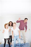 Family jumping on bed Stock Photo - Premium Royalty-Freenull, Code: 6102-07842923