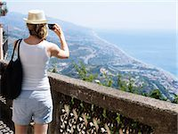 Woman taking picture of coastline Stock Photo - Premium Royalty-Freenull, Code: 6102-07843414